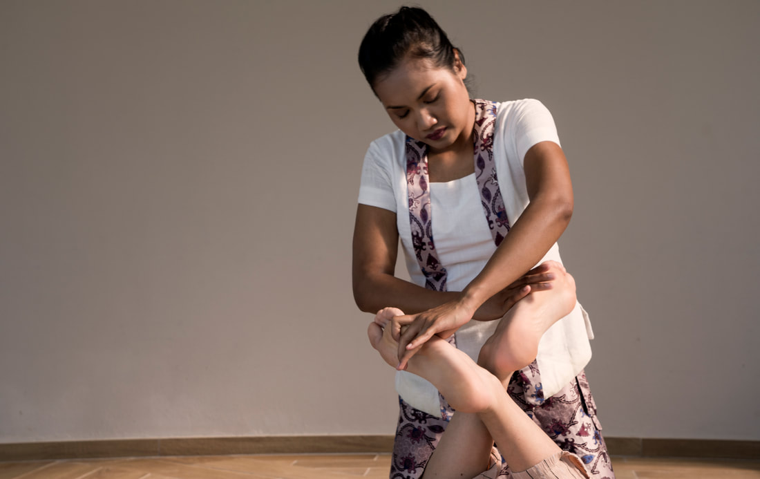 Massage Therapist administering a Thai massage